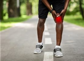 Cropped of black sportsman touching his inflamed knee highlighted with red, park background, copy space