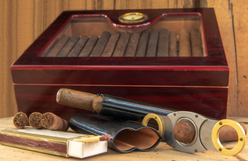 smoking accessories Quality cigars and other accessories such as cigar cutters, matches and cigar etui on a wooden table. In the background a humidor in front of a wooden wall. Concentrate on the cigars